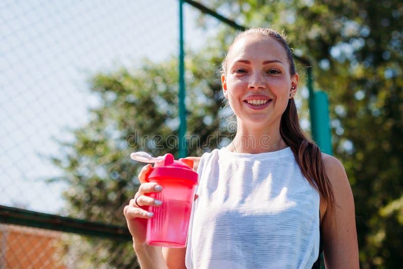 Sporty młoda blondynki kobieta z sporty szkłem z chłodno pouczającą wodą na sporta polu Ono uśmiecha się przy kamerą zdjęcia stock