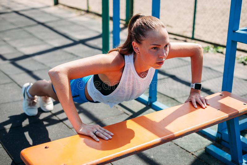 Sporty młoda seksowna kobieta robi UPS od ławka sportów gruntuje Pojęcie zdrowy styl życia zdjęcia stock