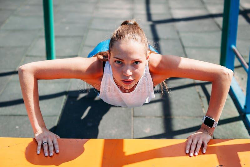 Sporty młoda seksowna kobieta robi UPS od ławki na sporta polu Pojęcie zdrowy styl życia obraz stock