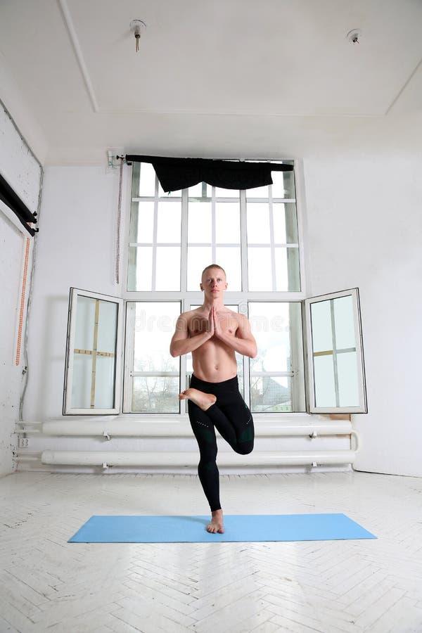 Sporty mężczyzna ćwiczy joga Vrikshasana, drzewna poza zdjęcia stock