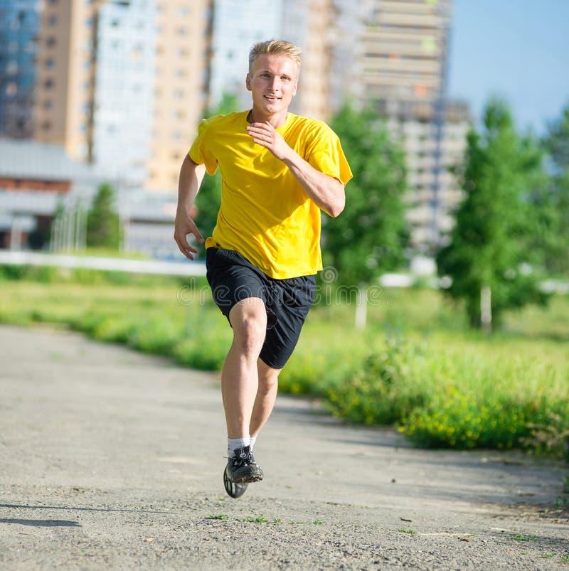 Sporty mężczyzna jogging w miasto ulicy parku Plenerowa Sprawność fizyczna zdjęcie stock