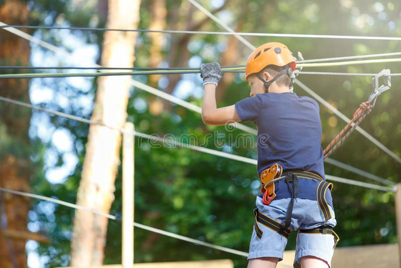 Sporty, młoda, śliczna chłopiec w białej t koszula, wydaje jego czas w przygody arkany parku w hełma i skrytki wyposażeniu w park obraz royalty free