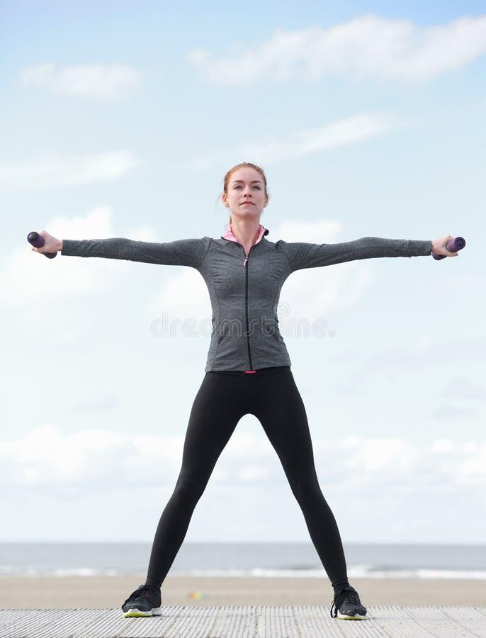 Sporty młoda kobieta ćwiczy z ciężarami fotografia royalty free