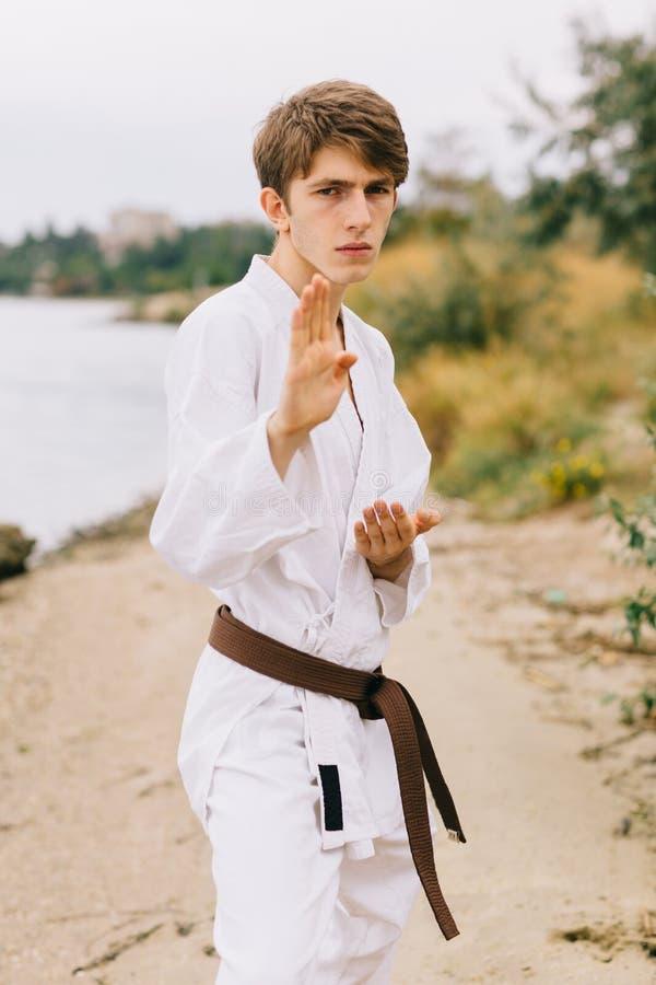 Sporty młody człowiek na outdoors karate szkoleniu Chłopiec w kimonie na naturalnym tle Ćwiczyć pojęcie obraz royalty free