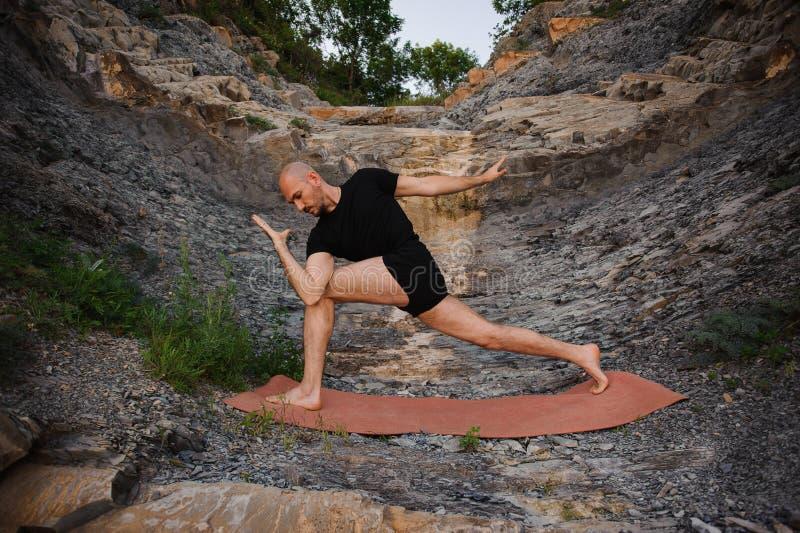 Sporty młody człowiek pracujący out, joga, robi Utthita Trikonasana, Przedłużyć trójbok pozę zdjęcia royalty free