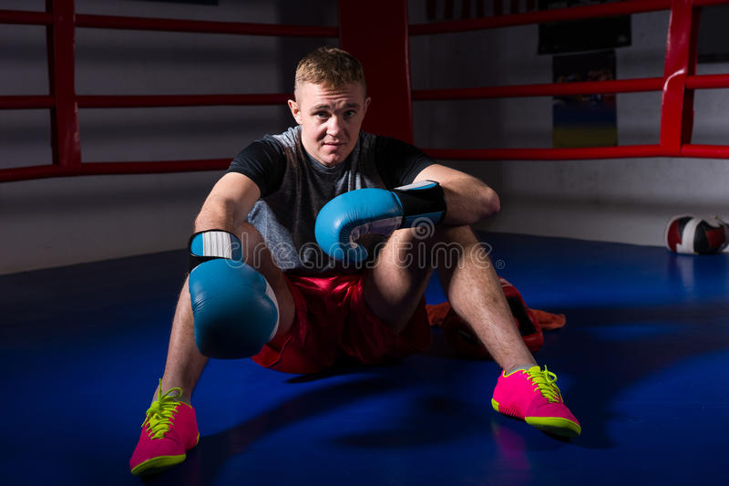 Sporty male boxer in boxing gloves sitting in regular boxing ring stock photos