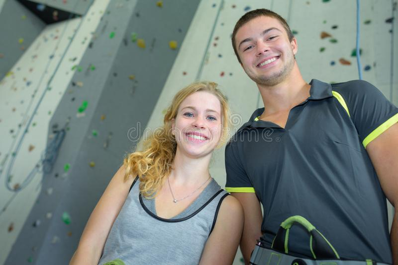 Sporty male and female posing at climbing wall stock photography