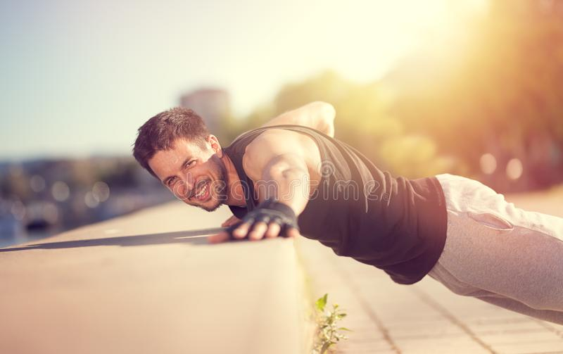 Sporty man doing push-ups on wall by river. Fitness muscular man doing a push-ups on wall by river royalty free stock photography