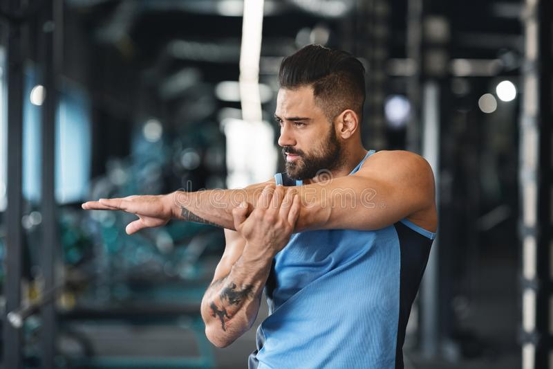 Sporty man at gym doing stretching exercises for hands stock photo