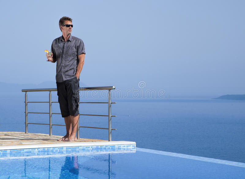 Sporty man in the infinity pool with drink royalty free stock photography