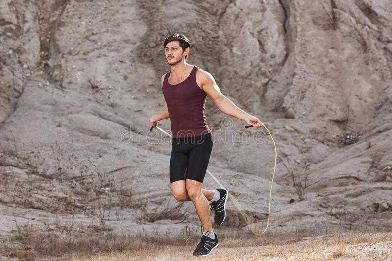 Sporty man jumping rope outdoors stock image
