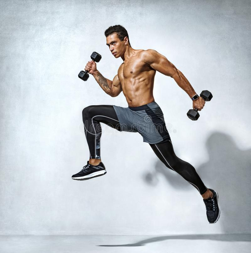Free Sporty Man Jumping With Dumbbells Royalty Free Stock Photography - 163305967