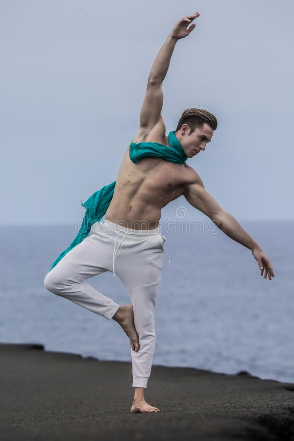 Athletic man raising hand and bending aside on one leg. Sporty man with naked torso and waving scarf on neck stretching hands up and standing on one leg at stock photos