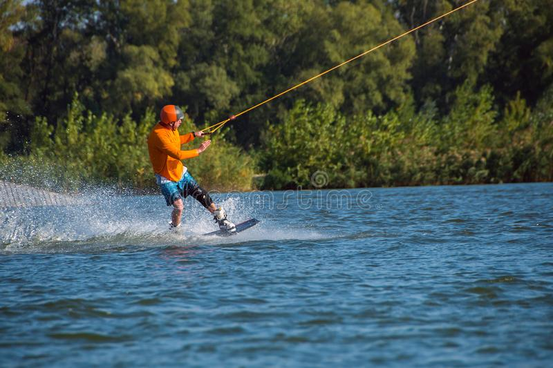 Sporty man is engaged in wakeboarding royalty free stock images