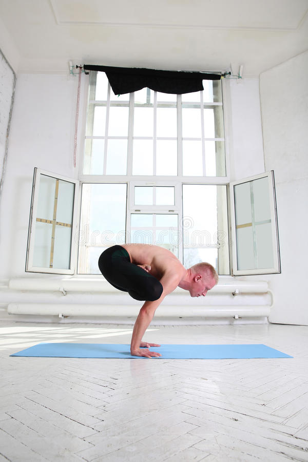 Sporty man practicing yoga. Handstand Urdhva Kukkutasana. Upward stock image