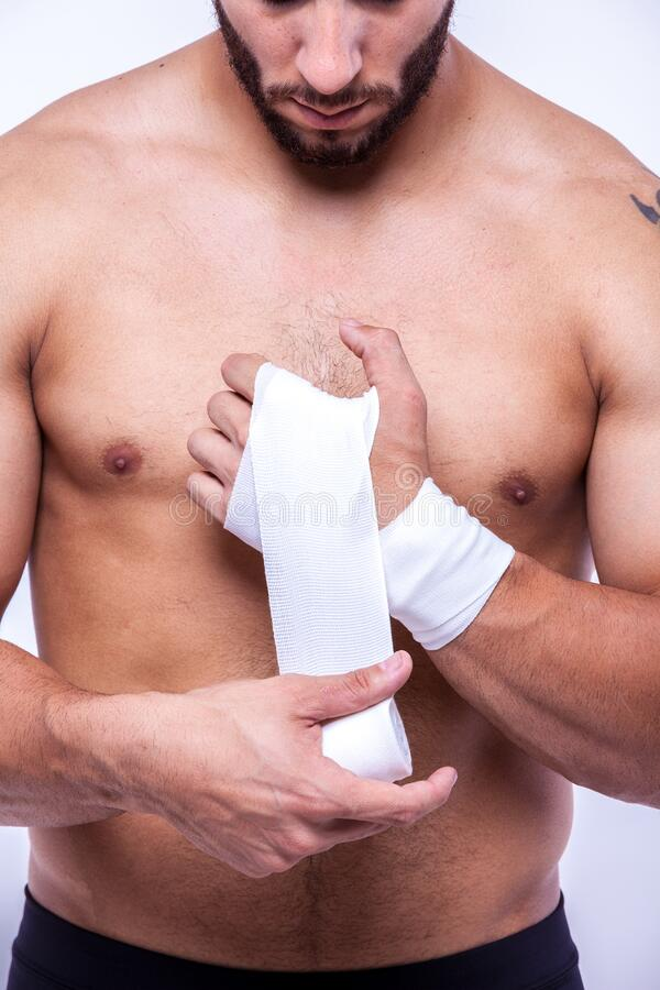 Sporty man rewinds his arms with an elastic bandage royalty free stock photo