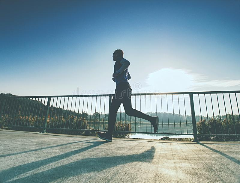 Sporty man run up the bridge . Sport and lifestyle concept royalty free stock images