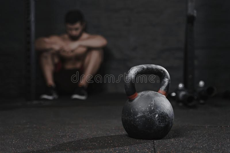 Sporty man sitting at the gym suffering breakdown to overcome. Demotivation sport concept.Stress and fatigue in sport. Crossfit k royalty free stock photography