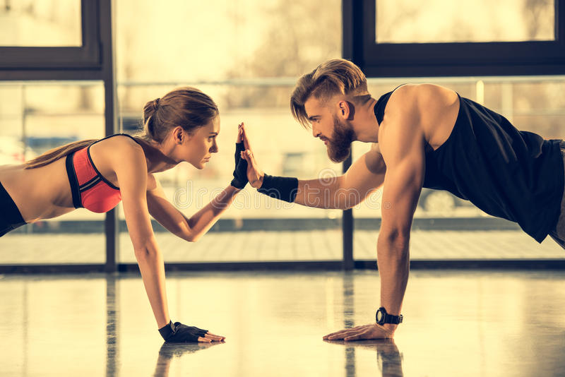 Sporty man and woman doing plank exercise and giving high five. Young sporty men and women doing plank exercise and giving high five royalty free stock photos