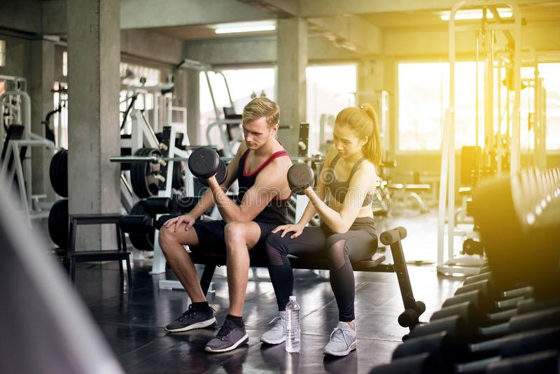 Sporty man and woman exercise lifting dumbbells together,Couple sport people in sportswear does the exercises at gym stock image