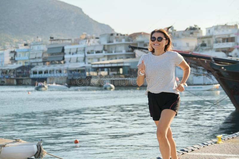 Sporty mature woman jogging running at seaside promenade stock photography