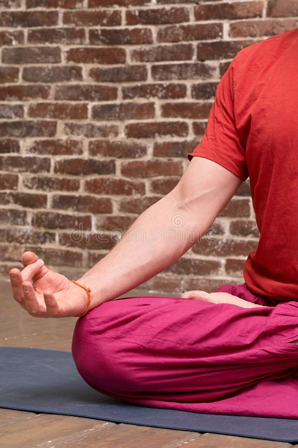 Sporty mindful man meditating alone on red brick wall background stock photos