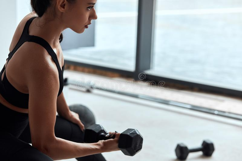 Young woman exercising lifting weights in gym. Arm muscles pumping stock photo