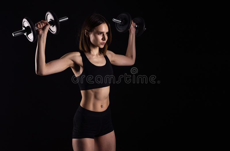 Sporty muscular female doing workout with dumbbells isolated on black background. Athletic young woman do a fitness workout with w. Eights royalty free stock image