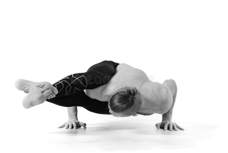 Sporty muscular young yogi man doing handstand, studio shot on white background, front view, full length, black and white royalty free stock images