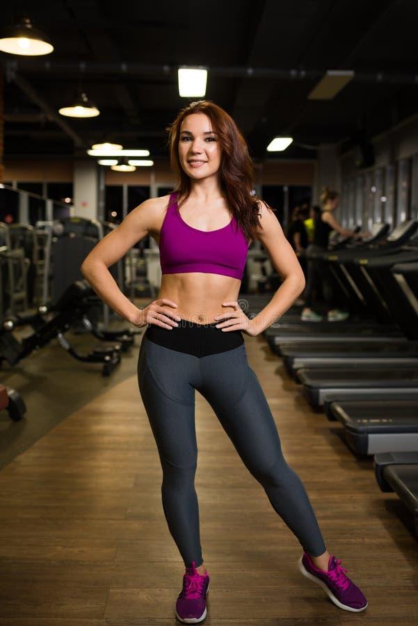 Sporty, nikła dziewczyny pozycja na tle ćwiczenie maszyny i karuzele w sportswear, fotografia royalty free