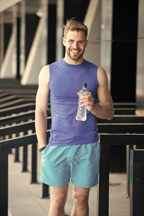 Sporty nutrition concept. Man athlete hold plastic bottle care hydration body after workout. Refreshing vitamin drink. Athlete drink water after training. Man stock image