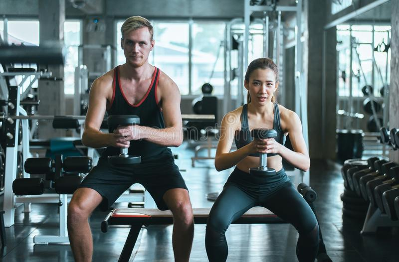Sporty pary kobieta i mężczyzna ćwiczymy z dumbbells lub robimy ćwiczeniom przy gym obraz royalty free