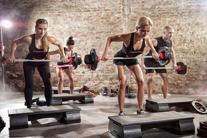 Sporty people doing exercise with weights royalty free stock image