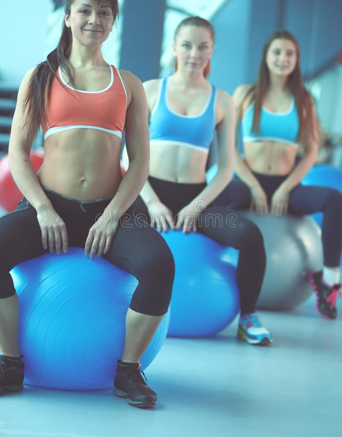 Sporty people sitting on exercise mats at a bright fitness studio. Sporty girls stock images