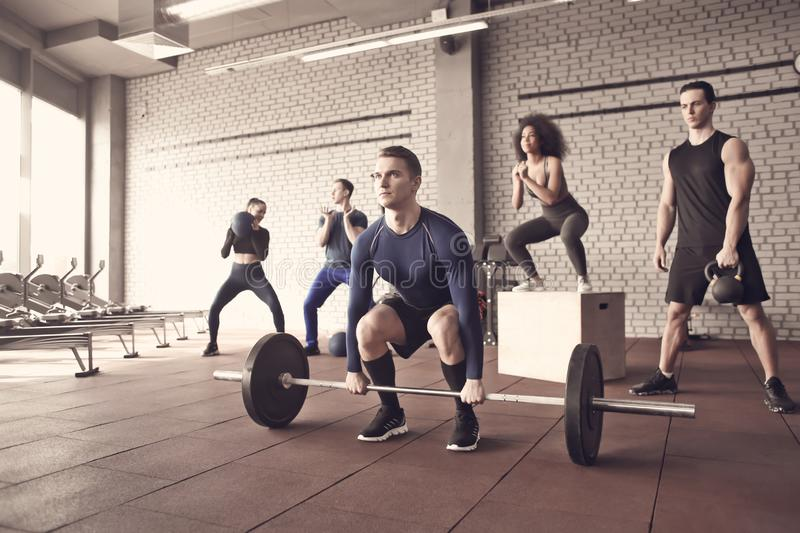 Sporty people training in a weight room royalty free stock photos