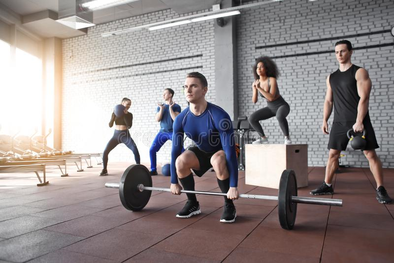 Sporty people training in a weight room royalty free stock photo