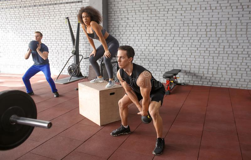 Sporty people training in a weight room royalty free stock photography