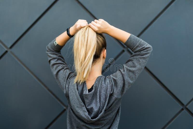 Sporty ponytail шнуровки женщины фитнеса и получать готовый для городской разминки или хода Задний взгляд спортсменки пригонки пр стоковые фото