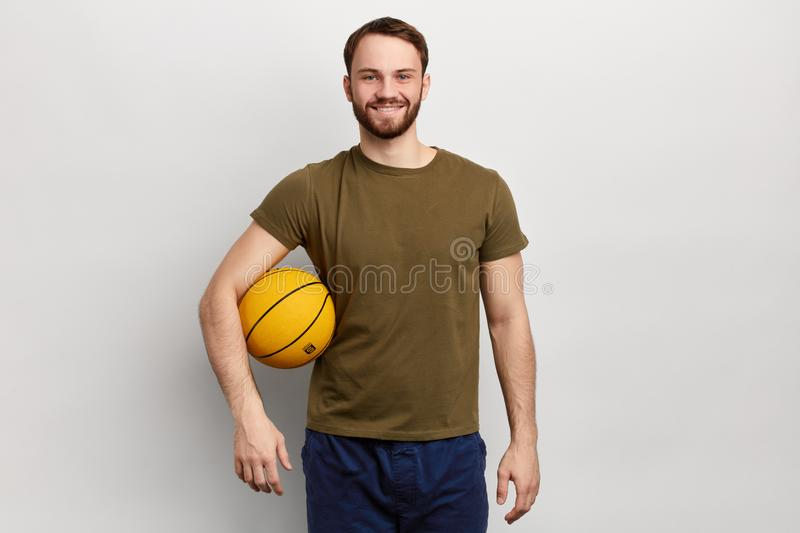 Sporty positive athlete with a ball looking at the camera royalty free stock photography