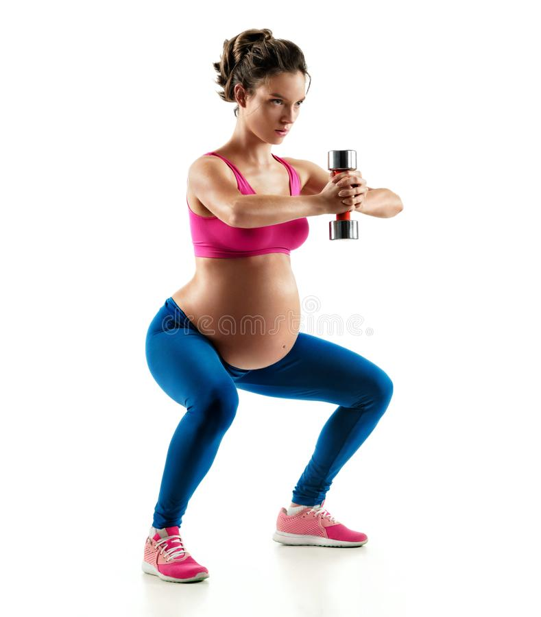Sporty pregnant girl squatting doing sit-ups with dumbbell isolated on white background. Concept of healthy life stock photography