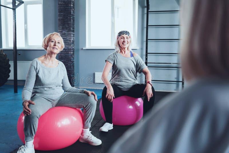 Sporty przechodzić na emeryturę damy siedzi na sprawności fizycznych piłkach podczas gdy trenujący zdjęcie royalty free