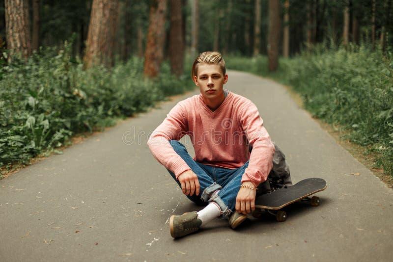 Sporty przystojny młody człowiek z deskorolka fotografia stock