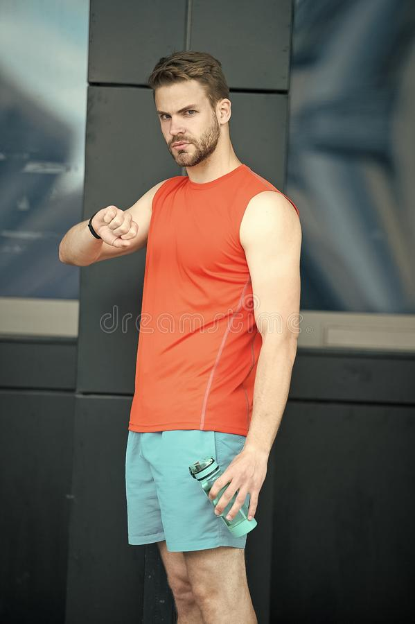 Sporty regime. Man athlete check time hold bottle care hydration body after workout. Drink regime water balance. Athlete. Drink water after training. Man stock images