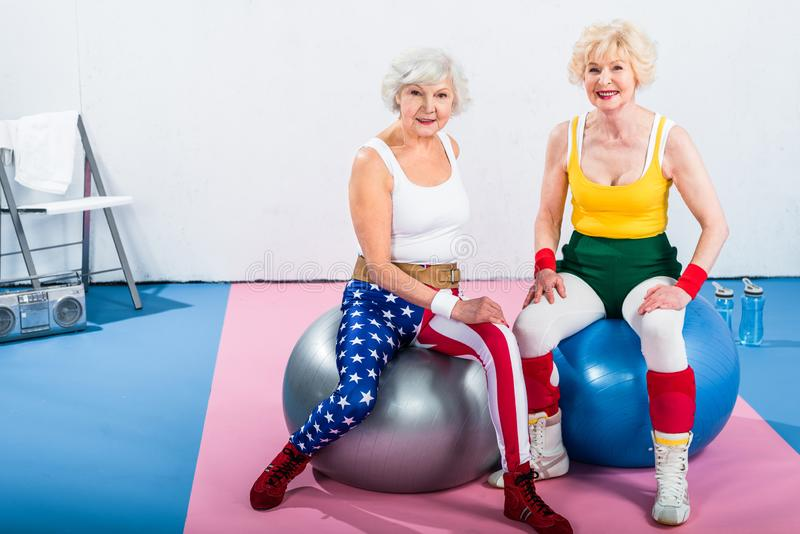 Sporty senior ladies in sportswear sitting on fitness balls and smiling. At camera stock photo