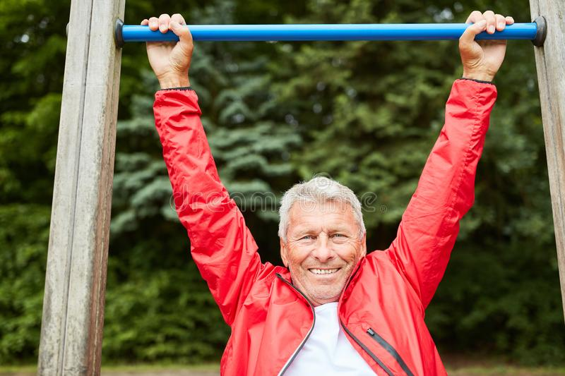 Sporty senior makes a chin-up royalty free stock photography