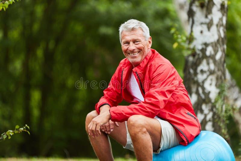 Sporty senior sits on gym ball stock image