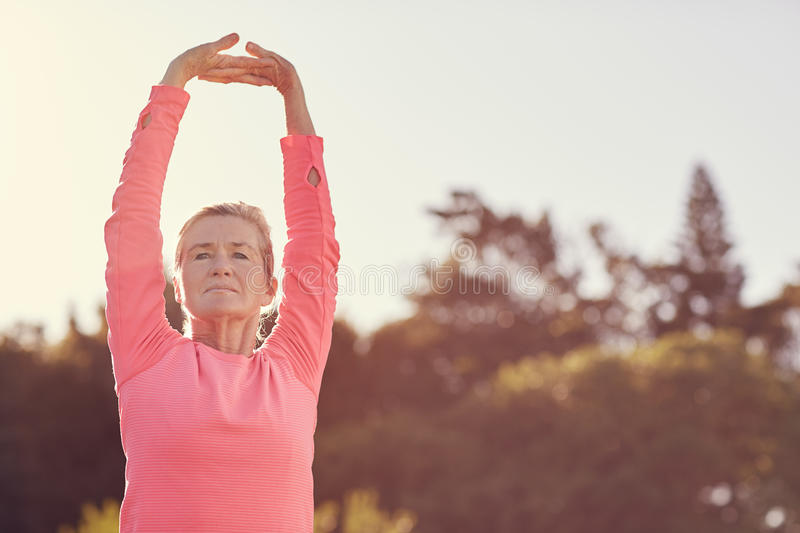 Sporty senior woman doing exercise warm-up stretches outdoors stock photo