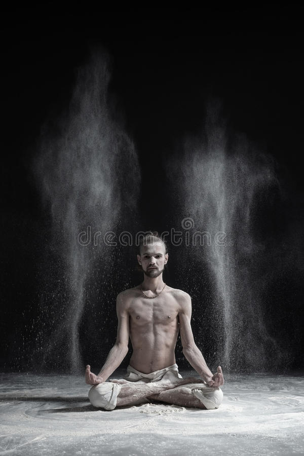 Sporty serene young man meditating sitting in cross-legged yoga lotus pose, Padmasana with palms in mudra. Dust flying in air. aghori concept royalty free stock images