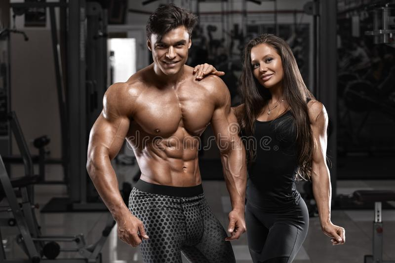 Sporty sexy couple showing muscle and workout in gym. Muscular man and wowan. Sporty sexy couple showing muscle and workout in gym. Muscular men and wowan royalty free stock images