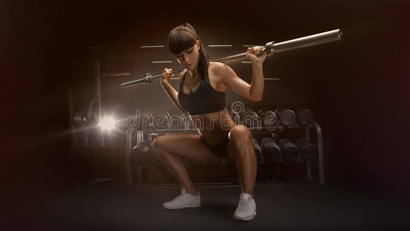 Sporty woman doing squat workout in gym. Sport, bodybuilding, lifestyle concept Fit young woman in great shape lifting barbells looking down, working out in a royalty free stock image